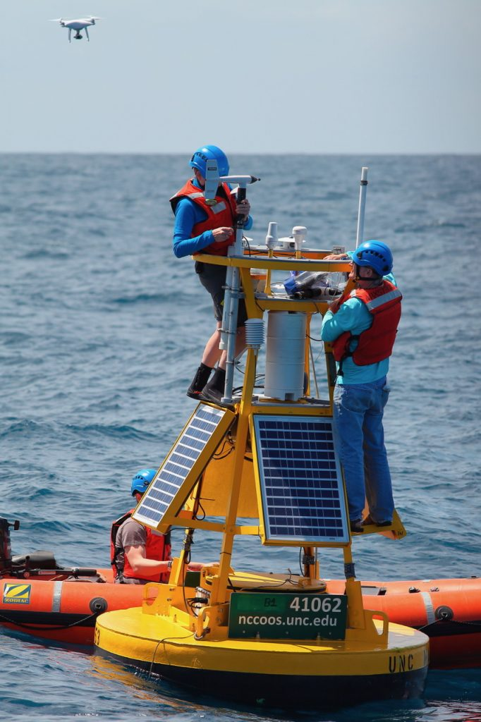 scientists working on buoy instruments
